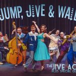 photo of cast in jump, jive and wail in front of a curtain